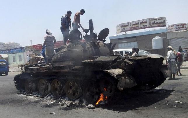 People stand on a tank that was burnt during clashes on a street in Yemen's southern port city of Aden